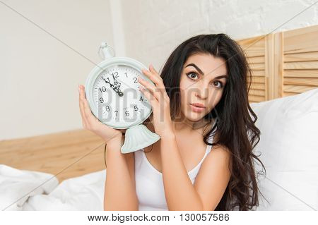 Young woman holding a big alarmclock with two hands on the bed