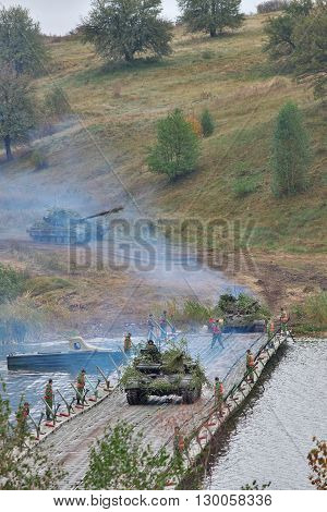 Zhitomir Ukraine - September 29 2010: Tanks cross the river over the pontoon ferry during the military trainings