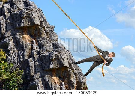 Business man climbs mountain within help of rope