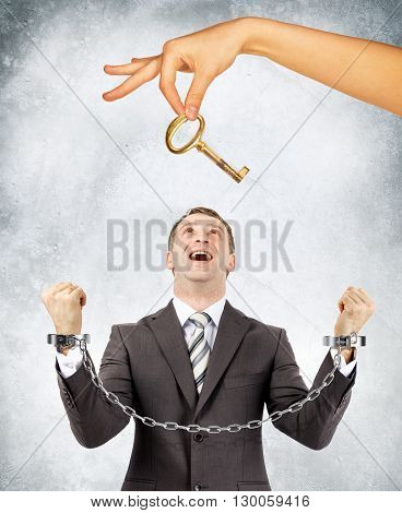 Happy businessman in handcuffs and big hand offering key