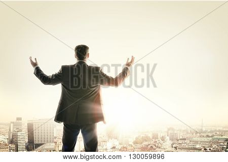 Happy businessman looks sunrise in city, concept for business