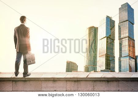 Businessman standing on roof and looking at sunrise, rear view