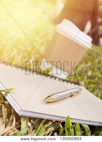 Pen notebook and hot paper cup of coffee on grass at the garden under sunlight with warm / soft color tone