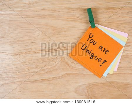Handwriting word You Are Unique on color note paper with wood background leadership business concept