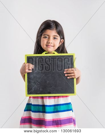 small indian girl holding and showing blank school slate, asian small girl with black school slate board