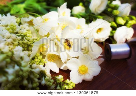 White flowers on a wooden table. Wasp, bee drinks nectar