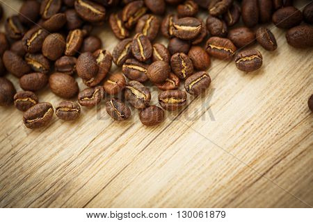 Coffee beans on a wooden desk lit by warm light (shallow DOF; color toned image)