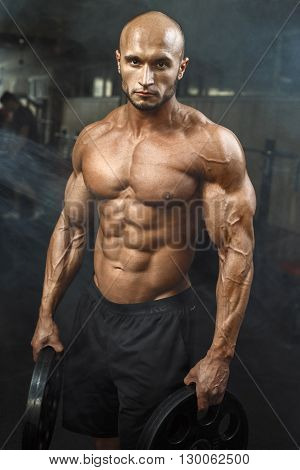 Very Power Athletic Guy Standing In Gym With Dumbbells And Lokking At Camera