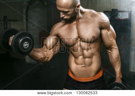 Very Powerfull Athletic Guy Working In Gym With Dumbbells