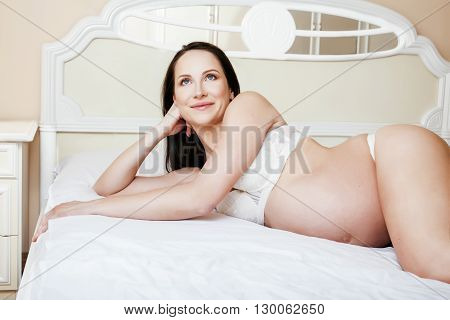 young pretty brunette pregnant woman laying in bed on white shirts interior, lifestyle people concept tenderness