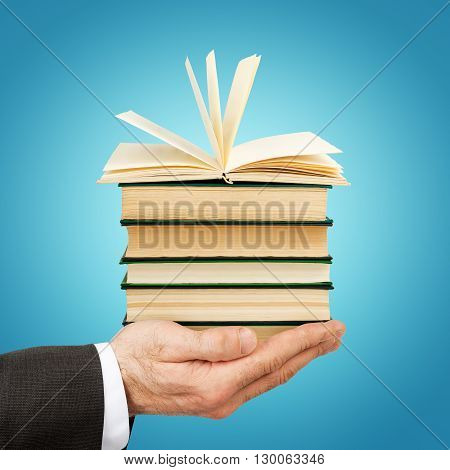 Business man holding stack of books with open one on blue background