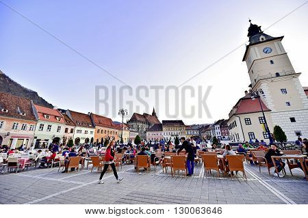 BRASOV ROMANIA - APRIL 3: Tourists in a weekend day spending time in Sfatului Square old town of Transylvania's medieval old town of Brasov on April 3 2016.