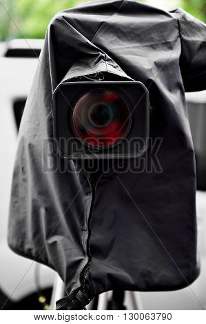 News camera on a tripod protected by a black rain cover