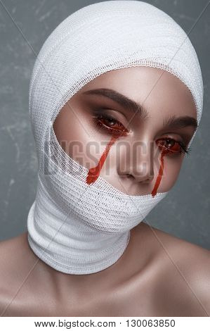 Fashion Beauty female Model with medical Halloween Makeup. Blood Drops from her Eyes and elastic Bandage on Head