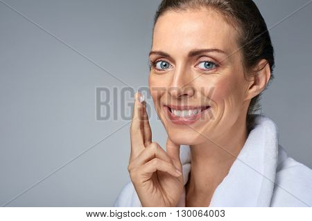 portrait of beautiful woman applying some cream to her face for skin care