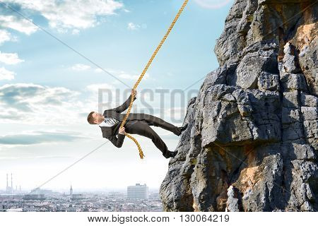Business man in suit climbs mountain with rope
