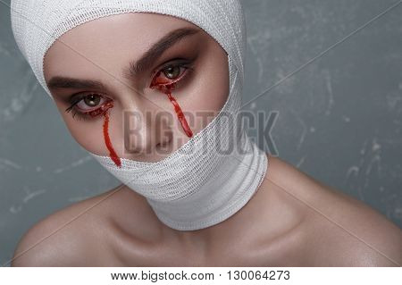 Scary Girl with Blood from her Eyes and white Bandage on Head and Mouth. Halloween Makeup