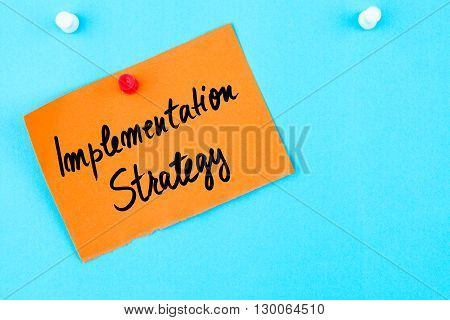 Implementation Strategy Written On Orange Paper Note