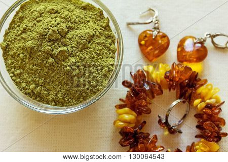 Henna powder. Still life with henna and amber jewelry. Focus on the powder.