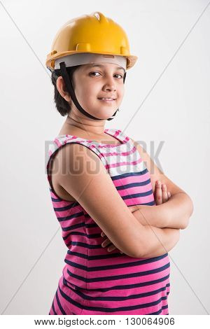 portrait of cute little indian girl in yellow hard hat and hands folded, asian small girl wearing yellow hard hat, isolated on white background