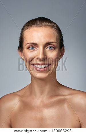 Smiling portrait of attractive middle age woman with natural make up, aging skin care concept