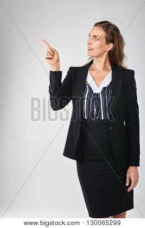 Woman in business suit pointing to the side isolated in studio, for product placement