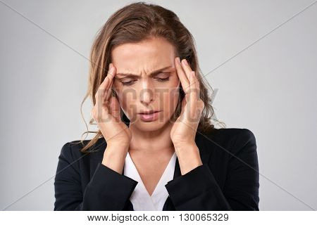 Stressful business woman massages her temple to ease her tension headache migraine head pain