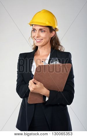Woman wearing hardhat safety helmet recording information on clipboard, architect surveyor engineer professional