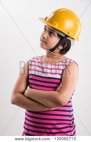 portrait of cute little indian girl in yellow hard hat holding paper roll, asian small girl wearing yellow hard hat and holding design plan, isolated on white background
