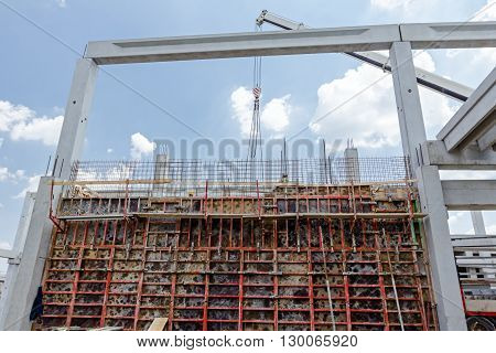 View on building site until workers are assembly a huge mold with reinforcement mesh for concreting.