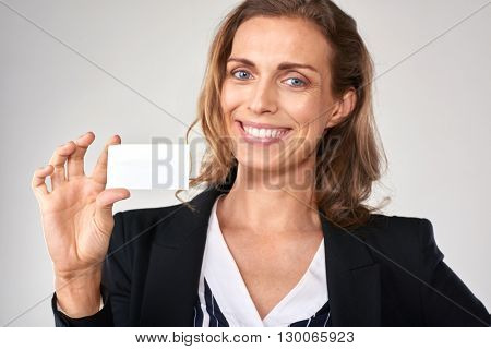 smiling businesswoman holding a blank card, copyspace for business details