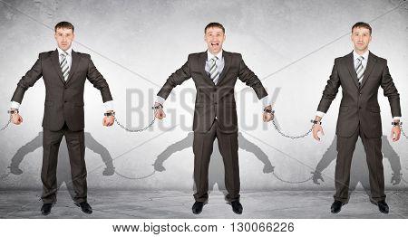 Set off businessmen in handcuffs on grey background
