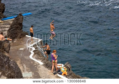 PORTO MONIZ, MADEIRA, PORTUGAL - AUGUST 25: people at the beach, on March 13, 2016 in Madeira Island, PORTUGAL