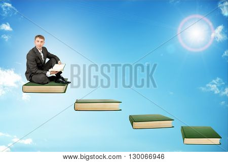 Young man in sitting on ladder steps with book in hands in sky