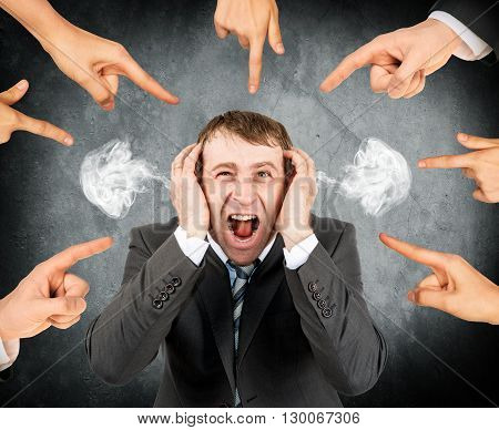 Many fingers pointing at screaming stressed businessman with smoke out his ears
