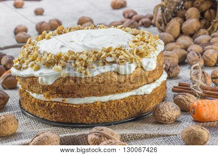 Carrot and Walnut Cake Topped with Cream on Jute Background with Walnuts Cinnamon and Carrots