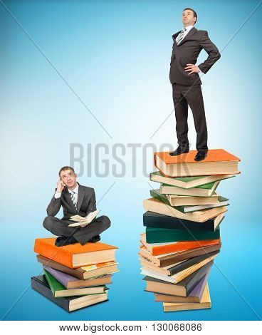 Proud businessman standing on stack of books with another man sitting on books