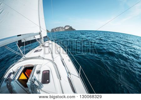 Yacht sailing in open sea at day with island