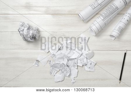 Architect drawing torn into small pieces and crumpled on a wooden surface. Top view composition. Workplace of architect or constructor. Engineering work. Failure. Construction and architecture. Architect drawing. Exact calculation. Anger sign.
