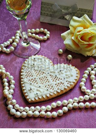Gingerbread glazed as a wedding invitation is on a table with white pearls, yellow rose and glass of wine