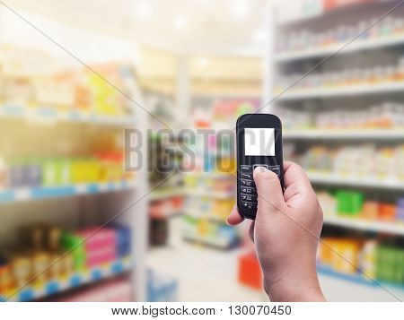 Hand with phone white screen on blurred in pharmacy background