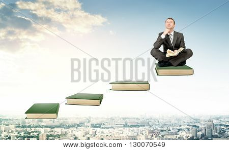 Young man in suit sitting on ladder steps with book in hands above city