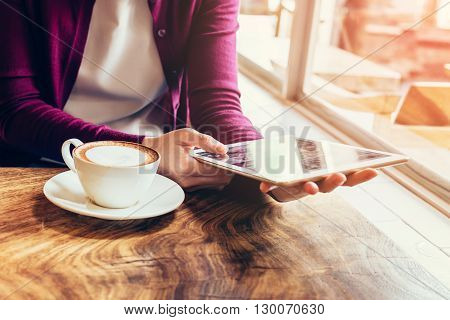 Woman Hands Using And Holding  Computer Tablet In Coffee Shop With Vintage Toned.