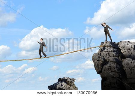 Image of businessman walking on rope above gap