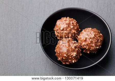 Chocolate candies, truffle in ceramic black bowl on grey slate background Copy space Top view