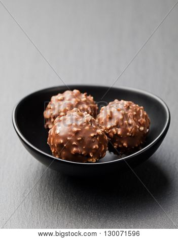 Chocolate candies, truffle in ceramic black bowl on grey slate background Copy space