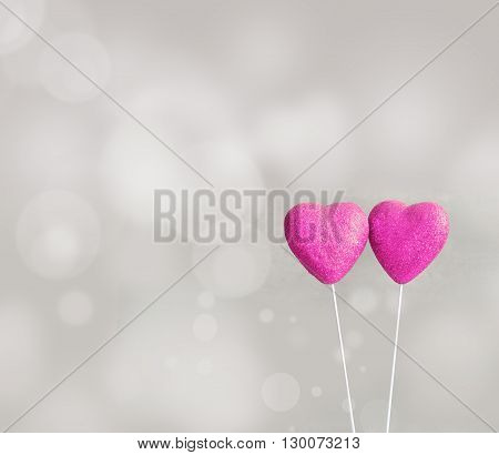 Two candy hearts in the white cup for Valentine's Day with grey background.