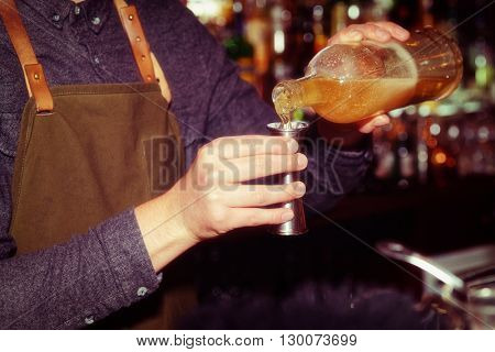 Old styled dartender is pouring liquor in metal jigger, toned image