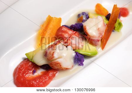 Lobster with sauce and vegetables on a white plate.