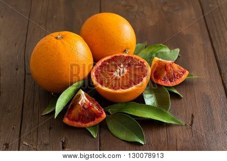 Fresh Sicilian oranges with leaves on a wooden table